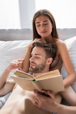 Shirtless man touching sexy girlfriend reading book in bedroom stock vector