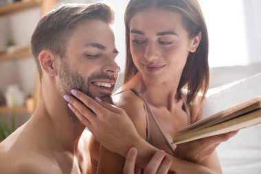 Smiling woman touching face of sexy boyfriend while holding book in bedroom stock vector