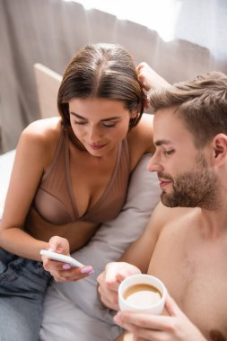 Young woman in bra showing smartphone to shirtless boyfriend on blurred foreground stock vector