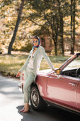 Fashionable woman in headscarf and sunglasses standing near cabriolet car on road