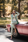 Elegant woman in sunglasses standing near vintage car on road
