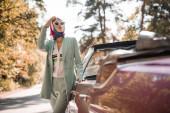 Mladá elegantní žena v slunečních brýlích dívá pryč v blízkosti auta na silnici na rozmazané popředí