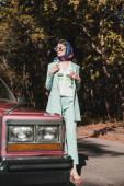 Divatos nő áll közel retro auto elmosódott előtérben az úton