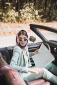 Elegantní žena s mapou dívá pryč v retro autě na rozmazané popředí během cesty