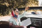 Elegantní žena drží mapu zatímco sedí v autě bez střechy na silnici na rozmazané popředí