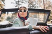 Stylová žena v slunečních brýlích drží mapu v retro autě na rozmazané popředí během cesty