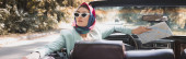 Stylish woman with map looking away in roofless car during road trip, banner