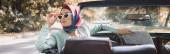 Žena s mapou dotýkající se slunečních brýlí v autě bez střechy na rozmazaném popředí, prapor