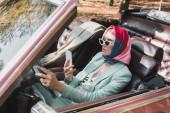 Elegáns nő használ okostelefon vezetés közben tető nélküli autó elmosódott előtérben