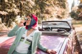 Stilvolle Frau lächelt, während sie auf dem Smartphone in der Nähe von dachlosem Auto auf der Straße spricht