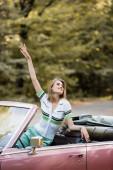 mosolygó nő néz félre, miközben ül a kabrió autó kéz a levegőben