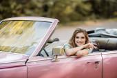 boldog fiatal nő ül retro kabrió autó és mosolyog a kamera