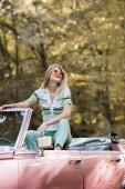 vzrušená žena v slunečních brýlích dívá pryč, zatímco pózuje v kabriolet auto v lese