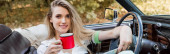 happy young woman smiling at camera while holding cup of coffee in convertible car, banner