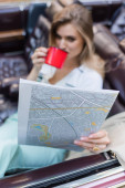 young woman looking at road atlas and drinking coffee while sitting in cabriolet on blurred background