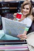 usmívající se žena drží mapu a šálek kávy, zatímco sedí v kabriolet na rozmazaném pozadí