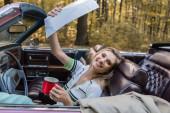 vzrušená žena dívá na kameru, zatímco drží šálek kávy a silniční atlas v kabriolet