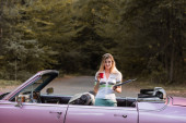stylová žena dívající se do kamery, zatímco drží mapu a šálek kávy v kabrioletu, banner