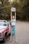 mladá usměvavá žena dívá na kameru, zatímco drží plakát s nápisem výlet v blízkosti vintage cabrio