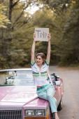 usmívající se žena drží plakát s nápisem výlet, zatímco sedí na kabrioletu a dívá se jinam
