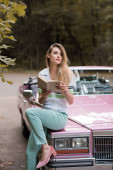 young woman looking away while sitting on hood of retro cabriolet and holding book on blurred background