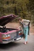 junge Frau schaut unter offener Motorhaube eines kaputten Oldtimers auf Straße