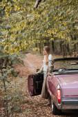 stylová žena dívá pryč, zatímco stojí u otevřených dveří kabriolet v lese