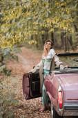 fiatal elegáns nő köpenyben nézi a kamerát, miközben áll közel vintage kabrió erdőben