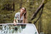 mladá žena dotýkající se slunečních brýlí a opírající se o přední sklo kabrioletů