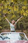 vzrušená žena v slunečních brýlích stojící s rukama ve vzduchu v kabrioletu