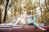 Lächelnde barfüßige Frau mit Sonnenbrille posiert in Cabrio-Auto im Wald
