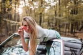 stylová mladá žena dotýkající se slunečních brýlí a opírající se o čelní sklo kabriolet