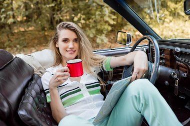 Young smiling woman looking at camera while sitting in convertible car with road atlas and cup of coffee stock vector
