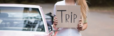 cropped view of woman holding card with trip lettering near vintage cabriolet on blurred background, banner