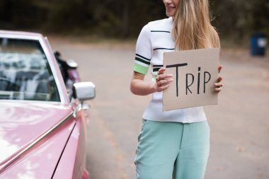 cropped view of woman holding card with trip lettering near cabriolet on blurred background