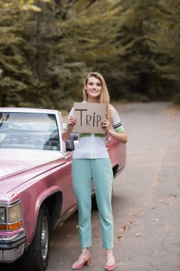 young stylish woman holding card with trip lettering near vintage convertible card
