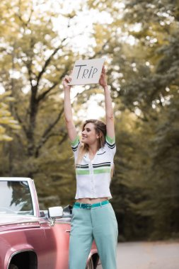 young woman holding placard with trip lettering in raised hands while standing near vintage convertible car