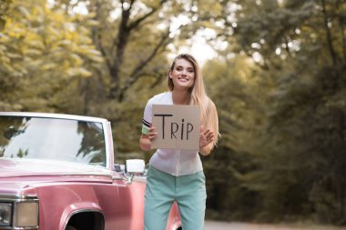 cheerful woman looking at camera while holding card with trip lettering near vintage convertible card