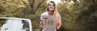 happy woman holding card with trip lettering near cabriolet, banner