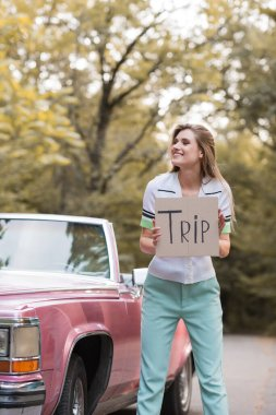 cheerful woman looking away while holding card with trip lettering near vintage convertible car