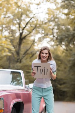 excited young woman holding placard with trip lettering near retro convertible car