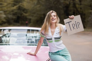 joyful woman sitting  on hood of vintage cabriolet and holding placard with trip lettering on blurred background