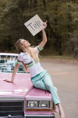 smiling woman holding placard with trip lettering while sitting on hood of cabriolet