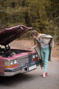 Young woman looking under open hood of broken vintage car on road stock vector