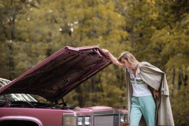Young woman in cape looking under open hood of broken vintage car stock vector