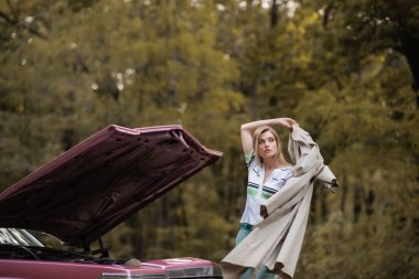 young woman putting cape on while standing near broken vintage car with open hood