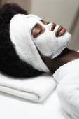 Nahaufnahme der lockigen Afroamerikanerin mit weißem Stirnband und Gesichtsmaske, die im Wellness-Salon liegt