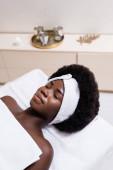 Fotografie Afroamerikanerin in weißem Haarband mit Bettlaken bedeckt auf Massagetisch im Wellness-Salon auf verschwommenem Hintergrund liegend