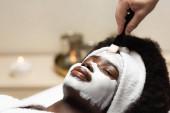Afričanky americká žena v čelence ležící v blízkosti lázeňské terapeut použití obličejové masky na čele na rozmazaném pozadí