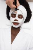 Fotografie Blick von oben auf positive afrikanisch-amerikanische Frau im Bademantel, liegend in der Nähe von Spa-Therapeut, der Gesichtsmaske auf der Stirn im Wellness-Salon aufträgt